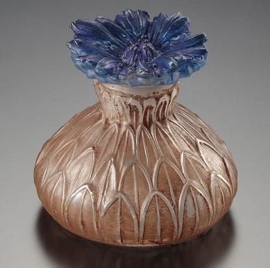 こちらは、当館所蔵のヤグルマギクをモチーフにした、リュシアン・ガイヤールが手掛けた香水瓶。クラミー社、デザイン1913年。